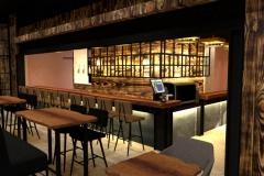 Zicht op de bar van Buck bar.kitchen. de wanden zijn in licht geblakerd hout - Shou Sugi Ban stijl